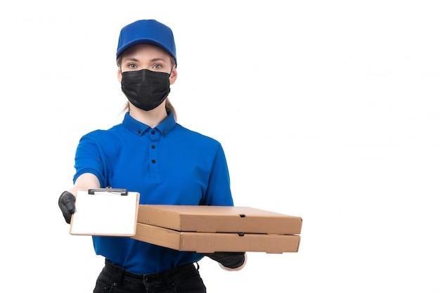 Een vooraanzicht jonge vrouwelijke koerier in blauwe uniforme zwarte handschoenen en zwart masker met voedselbezorgingspakketten
