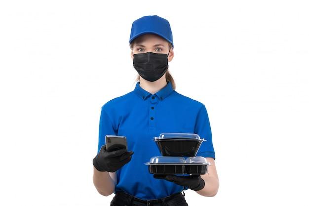 Een vooraanzicht jonge vrouwelijke koerier in blauwe uniforme zwarte handschoenen en zwart masker met voedselleveringskommen en telefoon