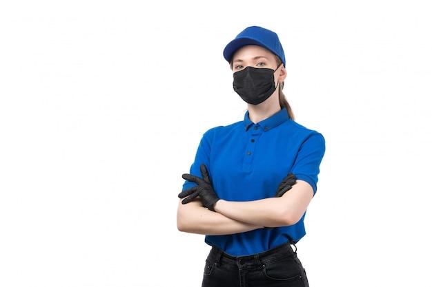 Een vooraanzicht jonge vrouwelijke koerier in blauwe uniforme zwarte handschoenen en zwart masker poseren