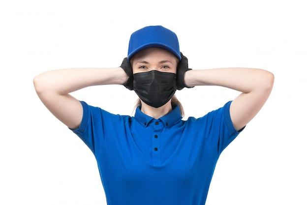 Een vooraanzicht jonge vrouwelijke koerier in blauwe uniforme zwarte handschoenen en zwart masker voor haar oren