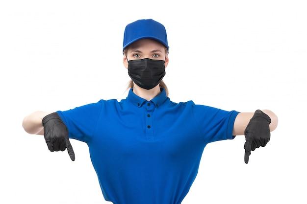 Een vooraanzicht jonge vrouwelijke koerier in blauwe uniforme zwarte handschoenen en zwart masker wijzende vingers