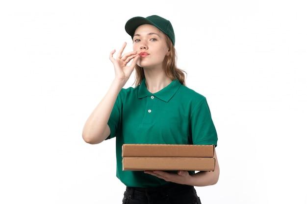 Een vooraanzicht jonge vrouwelijke koerier in de groene eenvormige doos die van de holdingspizza smakelijk teken toont