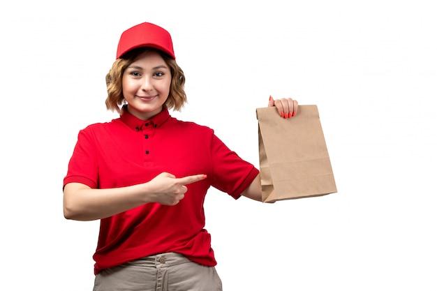 Een vooraanzicht jonge vrouwelijke koerier in eenvormig de leveringspakket van het holdingsvoedsel glimlachen