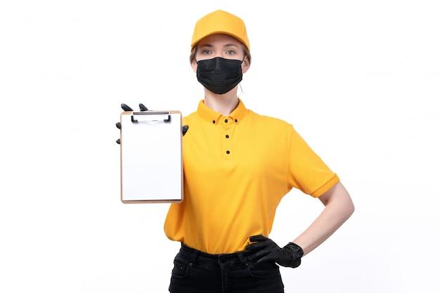 Een vooraanzicht jonge vrouwelijke koerier in gele uniforme zwarte handschoenen en zwart masker houden en blocnote tonen