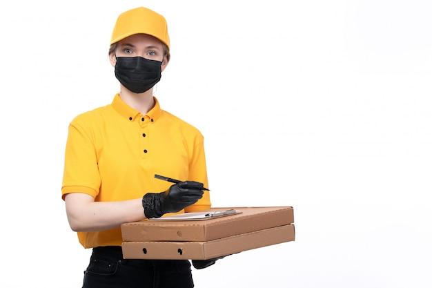 Een vooraanzicht jonge vrouwelijke koerier in gele uniforme zwarte handschoenen en zwart masker met blocnote voedseldozen en vraagt om de handtekening