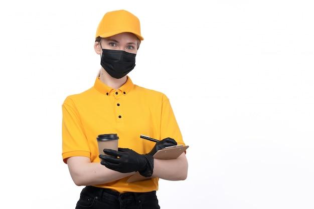 Een vooraanzicht jonge vrouwelijke koerier in gele uniforme zwarte handschoenen en zwart masker met koffiekopje en schrijfopdracht