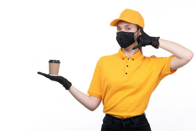 Een vooraanzicht jonge vrouwelijke koerier in gele uniforme zwarte handschoenen en zwart masker met koffiekopje om een oproep te vragen