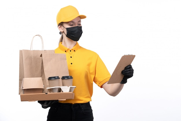 Een vooraanzicht jonge vrouwelijke koerier in gele uniforme zwarte handschoenen en zwart masker met voedselpakketten en koffiekopjes