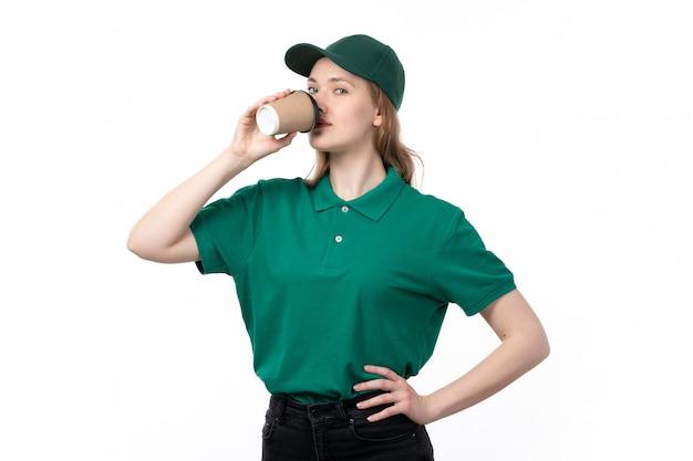 Een vooraanzicht jonge vrouwelijke koerier in groen uniform drinken koffie op wit