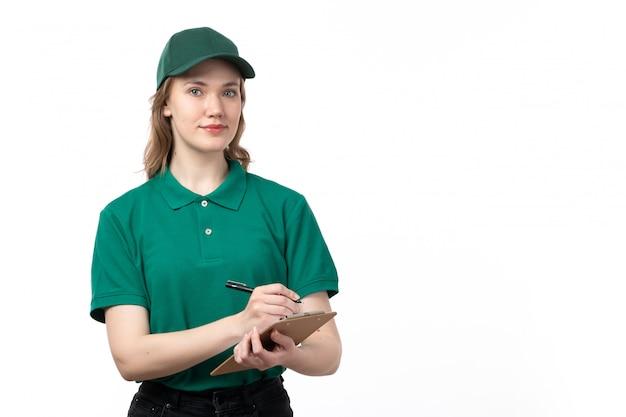 Een vooraanzicht jonge vrouwelijke koerier in groen uniform glimlachend bedrijf blocnote voor handtekeningen