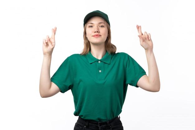 Een vooraanzicht jonge vrouwelijke koerier in groen uniform glimlachend poseren met gekruiste vingers