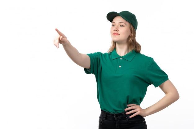 Een vooraanzicht jonge vrouwelijke koerier in groen uniform glimlachend wijzend in de verte