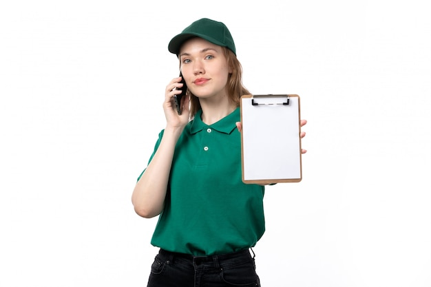 Een vooraanzicht jonge vrouwelijke koerier in groen uniform met blocnote voor handtekeningen tijdens het gesprek aan de telefoon