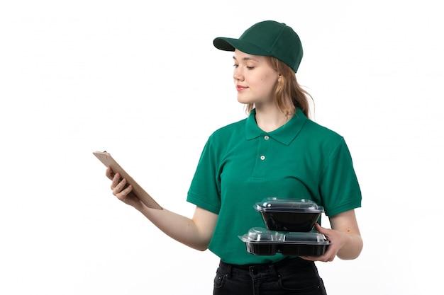 Een vooraanzicht jonge vrouwelijke koerier in groene uniform blocnote voor handtekeningen en kommen met voedsel glimlachen