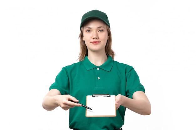 Een vooraanzicht jonge vrouwelijke koerier in groene uniform blocnote voor handtekeningen glimlachen