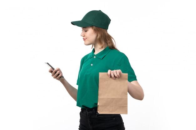 Een vooraanzicht jonge vrouwelijke koerier in groene uniforme glimlachende bedrijfsmartphone die het samen met voedselpakket gebruikt