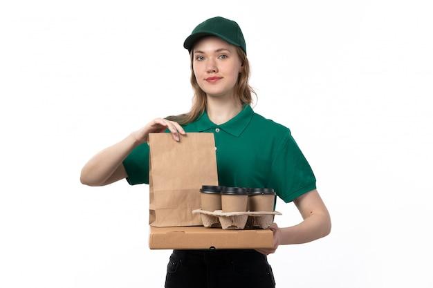 Een vooraanzicht jonge vrouwelijke koerier in groene uniforme koffiekopjes en voedselpakketten te houden