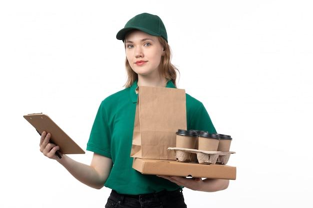 Een vooraanzicht jonge vrouwelijke koerier in groene uniforme koffiekopjes houden voedselpakketten en blocnote op wit