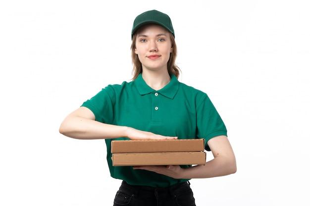 Een vooraanzicht jonge vrouwelijke koerier in groene uniforme pizzadozen houden en glimlachen