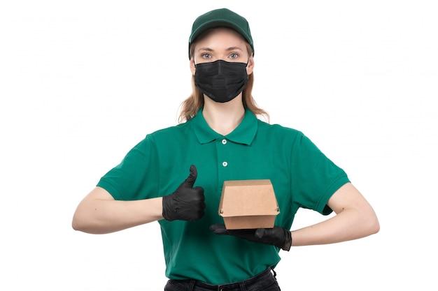 Een vooraanzicht jonge vrouwelijke koerier in groene uniforme zwarte handschoenen en een zwart masker met voedselbezorgingspakket
