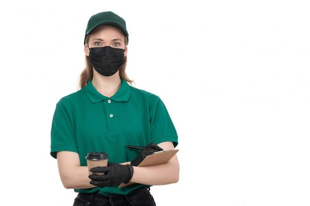 Een vooraanzicht jonge vrouwelijke koerier in groene uniforme zwarte handschoenen en zwart masker met koffiekopje en blocnote