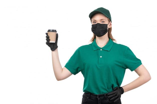Een vooraanzicht jonge vrouwelijke koerier in groene uniforme zwarte handschoenen en zwart masker met koffiekopje
