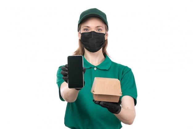 Een vooraanzicht jonge vrouwelijke koerier in groene uniforme zwarte handschoenen en zwart masker met voedselbezorgingspakket en telefoon
