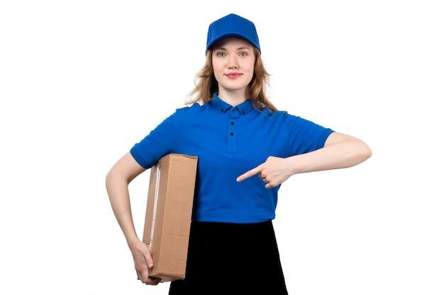 Een vooraanzicht jonge vrouwelijke koerier in het uniform glimlachen van de leveringsdoos