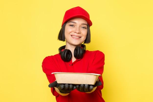Een vooraanzicht jonge vrouwelijke koerier in rode uniforme zwarte handschoenen en rode dop bedrijf etensbak met glimlach