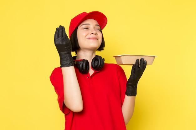 Een vooraanzicht jonge vrouwelijke koerier in rode uniforme zwarte handschoenen en rode dop houden etensbak met smakelijke meningsuiting