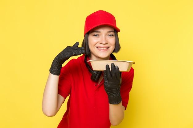 Een vooraanzicht jonge vrouwelijke koerier in rode uniforme zwarte handschoenen en rode dop houden etensbak