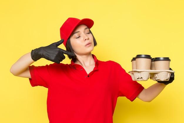 Een vooraanzicht jonge vrouwelijke koerier in rode uniforme zwarte handschoenen en rode dop met koffie cups