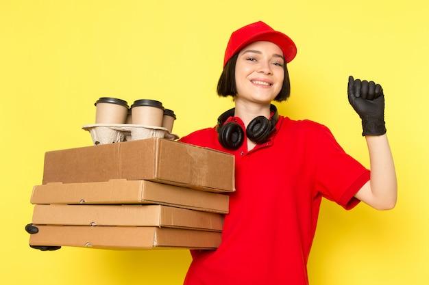 Een vooraanzicht jonge vrouwelijke koerier in rode uniforme zwarte handschoenen en rode dop met voedsel dozen en koffiekopje