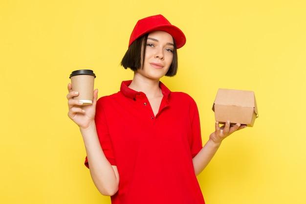Een vooraanzicht jonge vrouwelijke koerier in rode uniforme zwarte handschoenen en rode dop met voedseldoos en koffiekopje