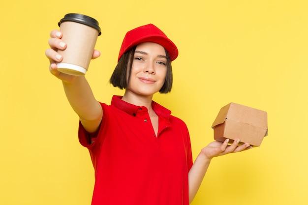 Een vooraanzicht jonge vrouwelijke koerier in rode uniforme zwarte handschoenen en rode dop met voedselpakket en koffiekopje