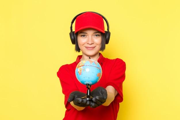 Een vooraanzicht jonge vrouwelijke koerier in rode uniforme zwarte handschoenen en rode pet met kleine wereldbol