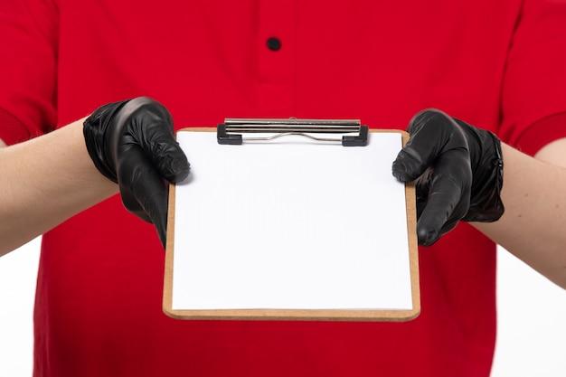 Een vooraanzicht jonge vrouwelijke koerier in rood overhemd en zwarte handschoenen die document nota houden