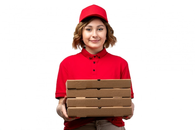 Een vooraanzicht jonge vrouwelijke koerier in uniform bedrijf pizza levering pakketten glimlachen