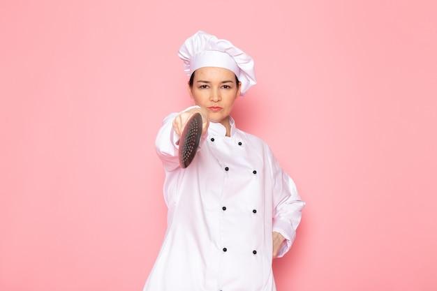 Een vooraanzicht jonge vrouwelijke kok in het witte kokkostuum witte glb stellen die de grote zilveren uitdrukking van de lepelbedreiging houden