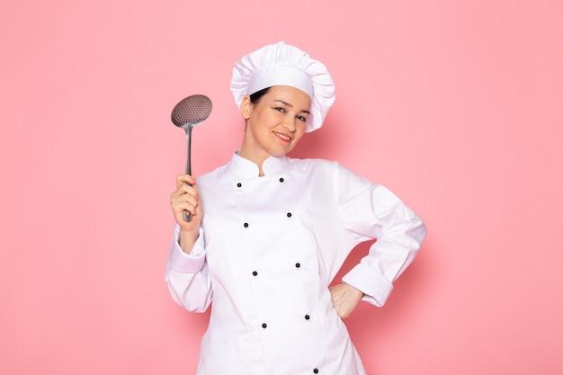 Een vooraanzicht jonge vrouwelijke kok in het witte kokkostuum witte glb stellen die het grote zilveren lepel glimlachen houden