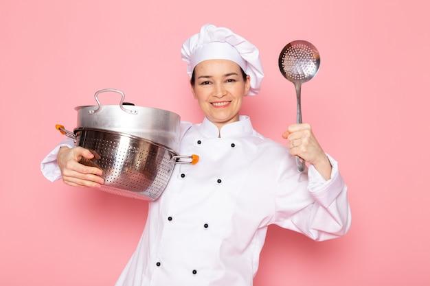 Een vooraanzicht jonge vrouwelijke kok in het witte kokkostuum witte glb stellen die zilveren steelpannen en maaltijdlepel het glimlachen houden