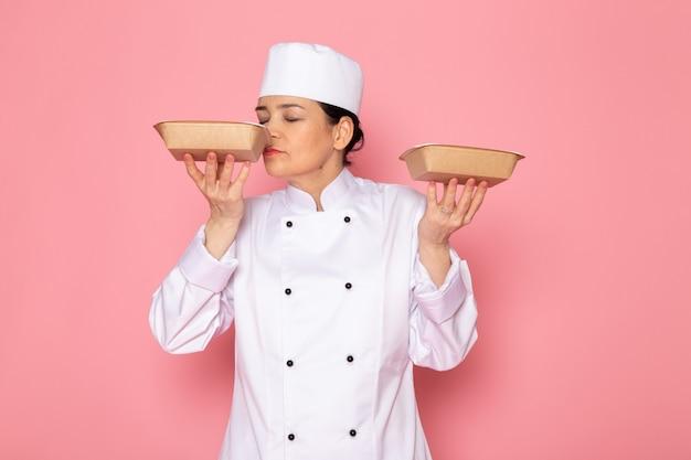 Een vooraanzicht jonge vrouwelijke kok in het witte kokkostuum witte glb stellende het houden van melk bruine kommen ruiken