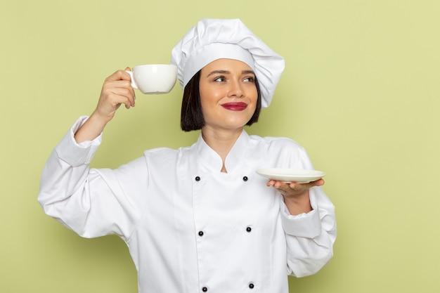 Een vooraanzicht jonge vrouwelijke kok in wit kokkostuum en glb die kop van koffie op de groene muur houden