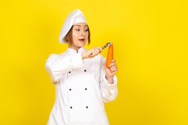 Een vooraanzicht jonge vrouwelijke kok in wit kokkostuum en wit glb die en oranje wortel op de geel houden schoonmaken