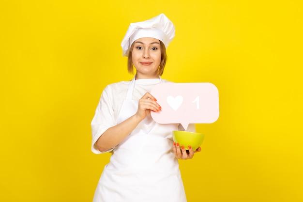 Een vooraanzicht jonge vrouwelijke kok in wit kokkostuum en wit glb die groene plaat en roze teken houden die op het geel glimlachen