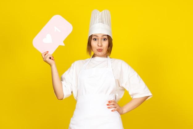 Een vooraanzicht jonge vrouwelijke kok in wit kokkostuum en wit glb die het roze teken stellen op het geel houden