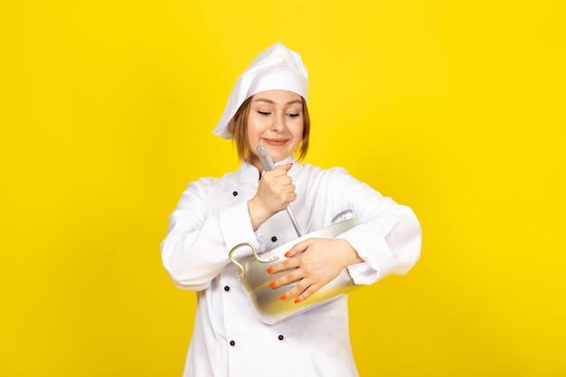 Een vooraanzicht jonge vrouwelijke kok in wit kokkostuum en wit glb die om zilveren pan houden die op het geel glimlachen