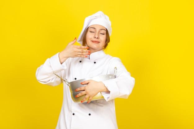 Een vooraanzicht jonge vrouwelijke kok in wit kokkostuum en wit glb die om zilveren pan houden die op het geel ruiken