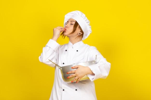 Een vooraanzicht jonge vrouwelijke kok in wit kokkostuum en wit glb die om zilveren pan houden die smakelijk teken op het geel uitdrukken