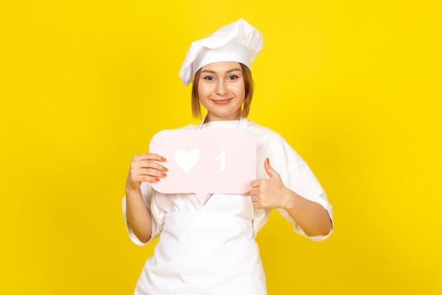 Een vooraanzicht jonge vrouwelijke kok in wit kokkostuum en wit glb die roze teken houden glimlachend op het geel